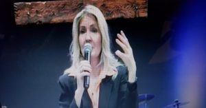 Photo of Melissa Holy with microphone as key-note speaker for leadership training.