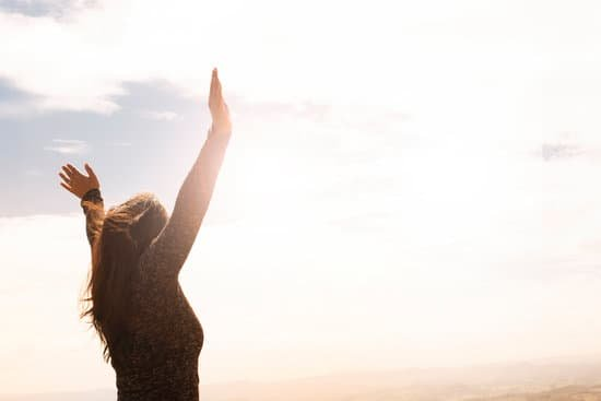 Image of joyous woman with hands raised high in the air standing strong in courage and grit.