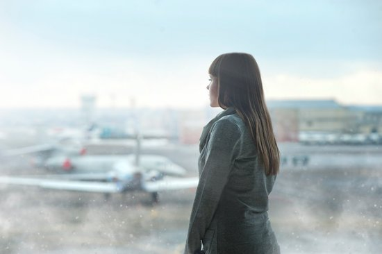 Image of woman peering out window looking at airplane in the rain. Thinking of launching into bigger things.