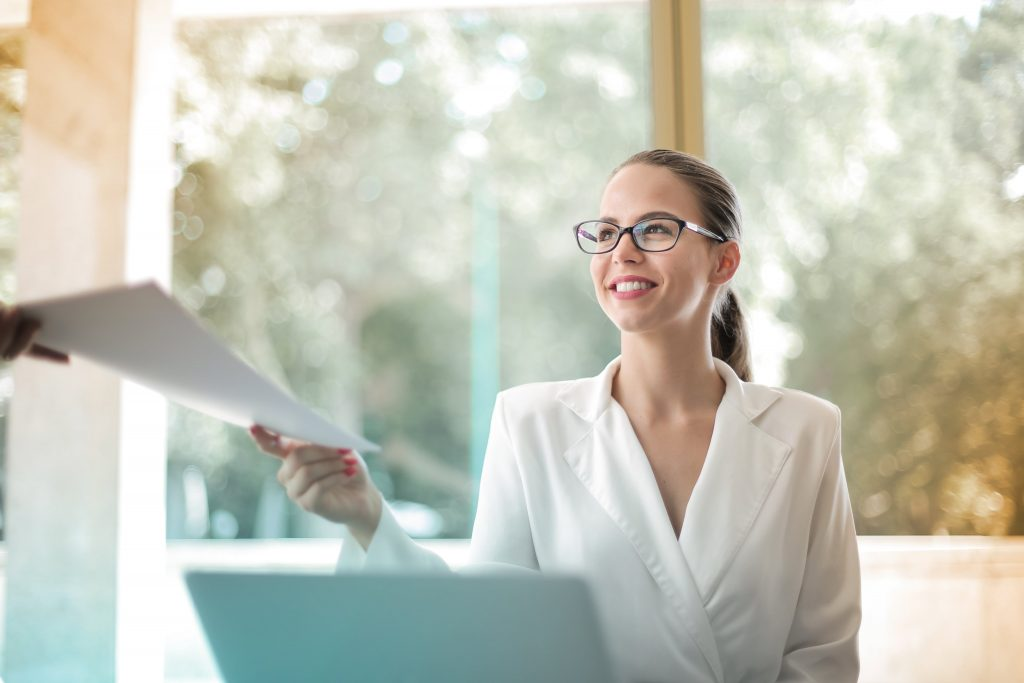 Positive business woman doing paperwork in office
