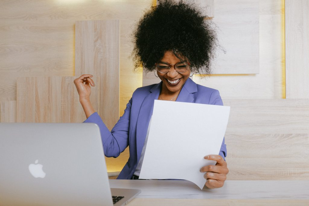 Happy woman at computer desk reads work documents