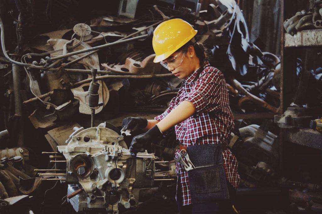 Woman in yellow hard hat working in an industrial job