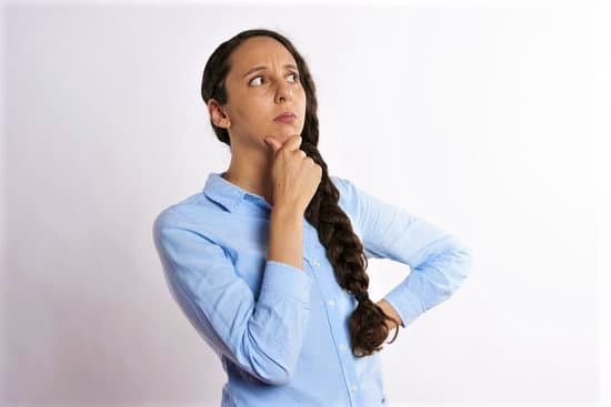 Woman standing with hand on her chin thinking and preparing how to handle pressure on the job.