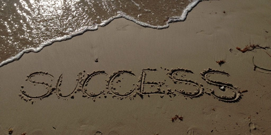 The word SUCCESS written in sand at the beach, words of encouragement