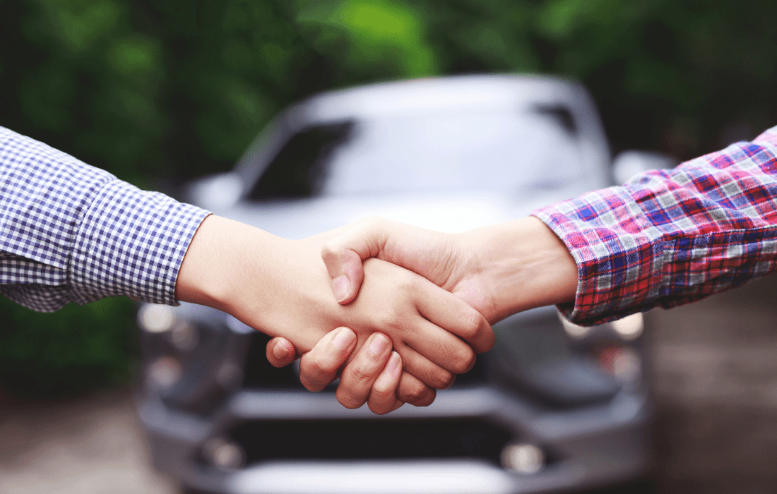 2 people shaking hands in front of a car after successful sale.