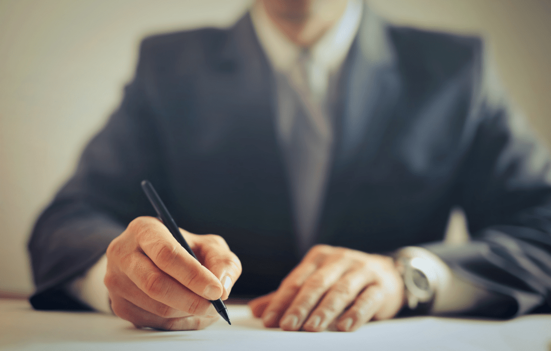 Young businessman at desk signing paperwork and focused on true success.
